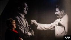 Женщина у изображения Адольфа Гитлера и Иосифа Сталина на выставке в музее Второй мировой войны в польском городе Гданьске.