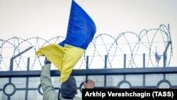 Украина туын қоршауға тікпек болып тұрған адам (Көрнекі сурет)