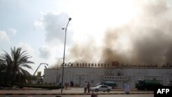 Protesters sit near a burning supermarket during a demonstration calling for jobs and reform in Sohar on February 28.