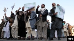On October 24 Afghans, including religious clerics, hold placards and shout slogans during a protest in Kabul against an allegedly blasphemous article which appeared in the Afghanistan Express newspaper.