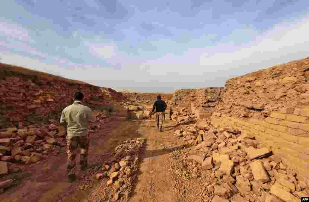Soldiers walk through the ancient ruins.