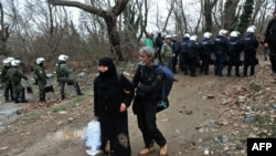 Migrants pass security forces on their way to Macedonia and the Balkans route to the European Union