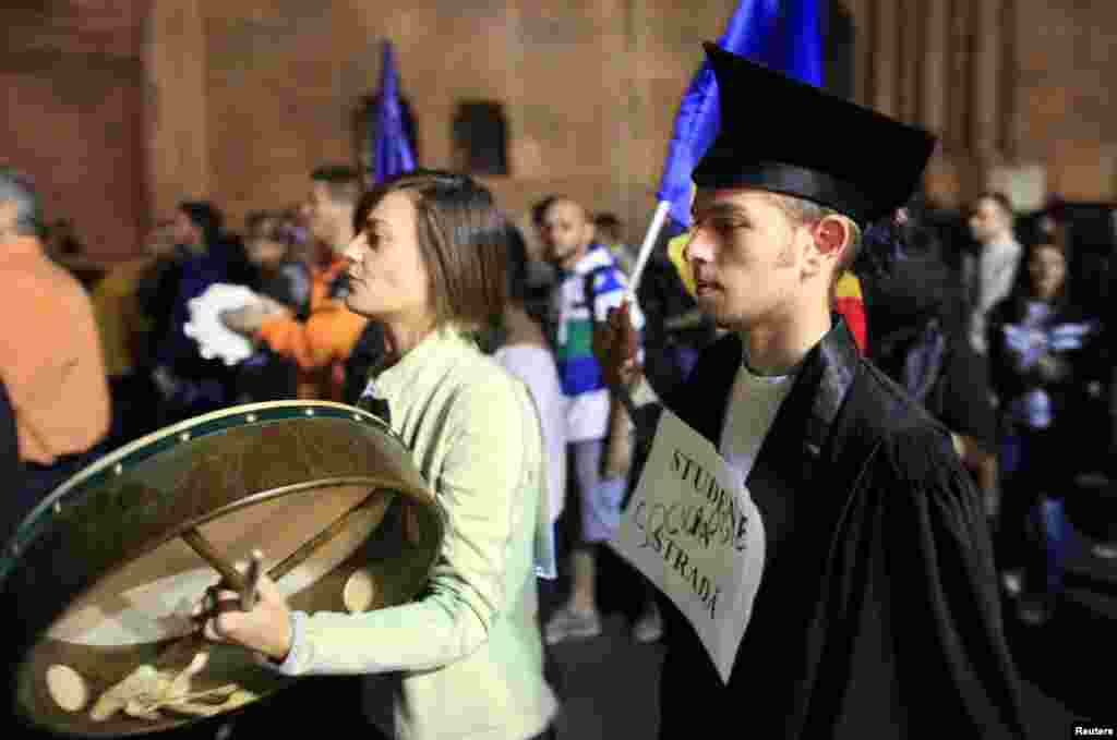 An antimining demonstrator beats a drum in protest as they march on downtown streets in Bucharest. (Reuters/Radu Sigheti)
