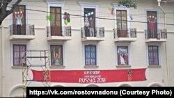 Нарисованные болельщики на баннере, закрывающем полуразрушенный дом в центре Ростова-на-Дону