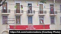 На баннере, закрывающем полуразрушенный дом в центре Ростова-на-Дону, нарисованы болельщики