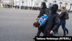 Полиция өкілдері қарсылық акциясы кезінде ұсталған адамды әкетіп барады. Санкт-Петербург, 5 мамыр 2018 жыл.