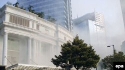 People evacuate as a bomb explodes at the Ritz Carlton hotel in Jakarta on July 17