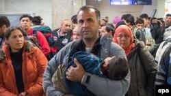 Отец и сын из Сирии ждут автобуса на железнодорожном вокзале в Шонефельде, чтобы продолжить свой дальнейший путь в Европу. Германия, 28 сентября 2015 года.