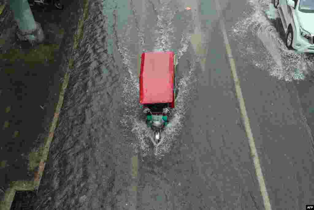 A tricycle makes its way along a flooded street in Beijing, which was hit with heavy rains this week. (AFP)