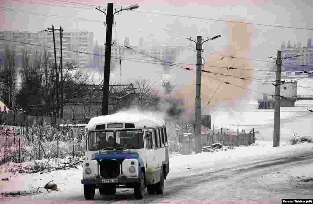 За автобусом виден дым от взрыва снаряда – во время штурма города российские войска использовали артиллерию и танки.Грозный, 24 января 1995 года.
