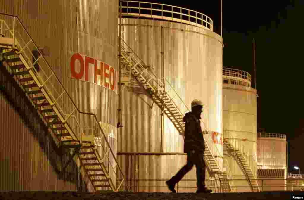 Рабочий рядом с нефтехранилищем, находящимся на месторождении в Кызылординской области.