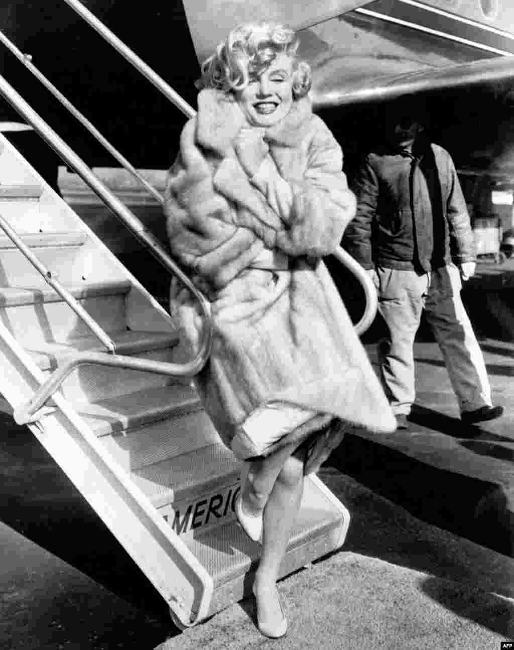 "Monroe poses for photographers at New York's La Guardia Airport before flying to Chicago for the presentation of her film ""Some Like It Hot"" in 1959."