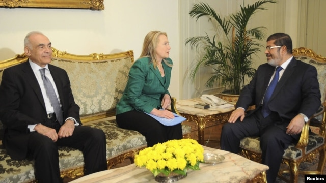 Egypt's Foreign Minister Mohamed Kamel Amr (left to right), U.S. Secretary of State Hillary Clinton, and Egyptian President Muhammad Morsi meet at the presidential palace in Cairo on November 21.