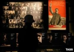 """Портреты жертв """"большого террора"""" и плакат со Сталиным в музее в Тбилиси."""