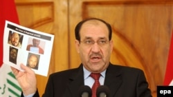 Iraqi Prime Minister Nuri al-Maliki displays photographs showing the body of Abu Omar al-Baghdadi during a news conference today.