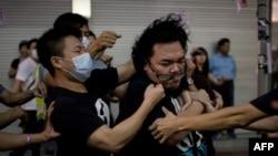 Люди в масках держат мужчину, который пытался помешать разбору баррикад, возведенных демонстрантами.