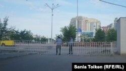 Двое полицейских стоят у ограждения на центральной площади в Атырау. 22 мая 2016 года.