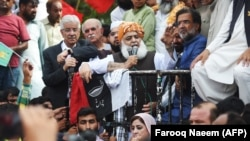 Pakistan opposition leader Maulana Fazl-ur-Rehman (C) addresses protesters outside the election commission office against the alleged election rigging in Islamabad on August 8.
