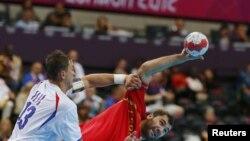 Испанский спортсмен Джон Канеллас (справа) и сербский спортсмен Момир Илич Сербии во время матча мужского гандбола на Олимпийских играх в Лондоне, 29 июля 2012 года.