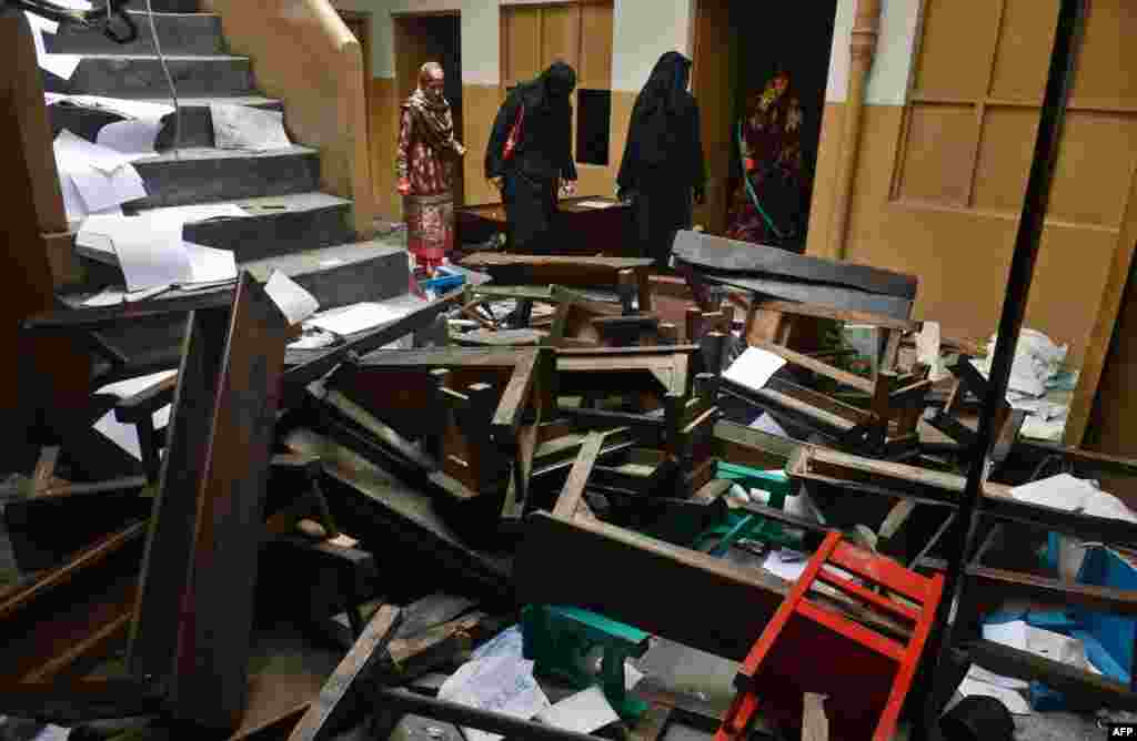 Teachers inspect the wreckage of a burned-out school in Lahore on November 3 after it was set on fire by an angry mob alleging that the school gave a test that insulted the Prophet Mohammed.