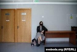 Дачка Асіпцова Яніна сядзіць каля дзьвярэй залі суду. Ёй не хапіла месца з-за абмежаваньня на прысутнасьць толькі аднаму чалавеку з падтрымкі