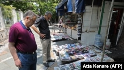 People reading headlines in front of a newspaper stand in the Iranian capital Tehran, May 20, 2019 - FILE PHOTO