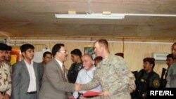ممثل رئاسة الوزراء سمير حدداد يتسلم اتفاقية استلام القاعدة من ضابط أميركي