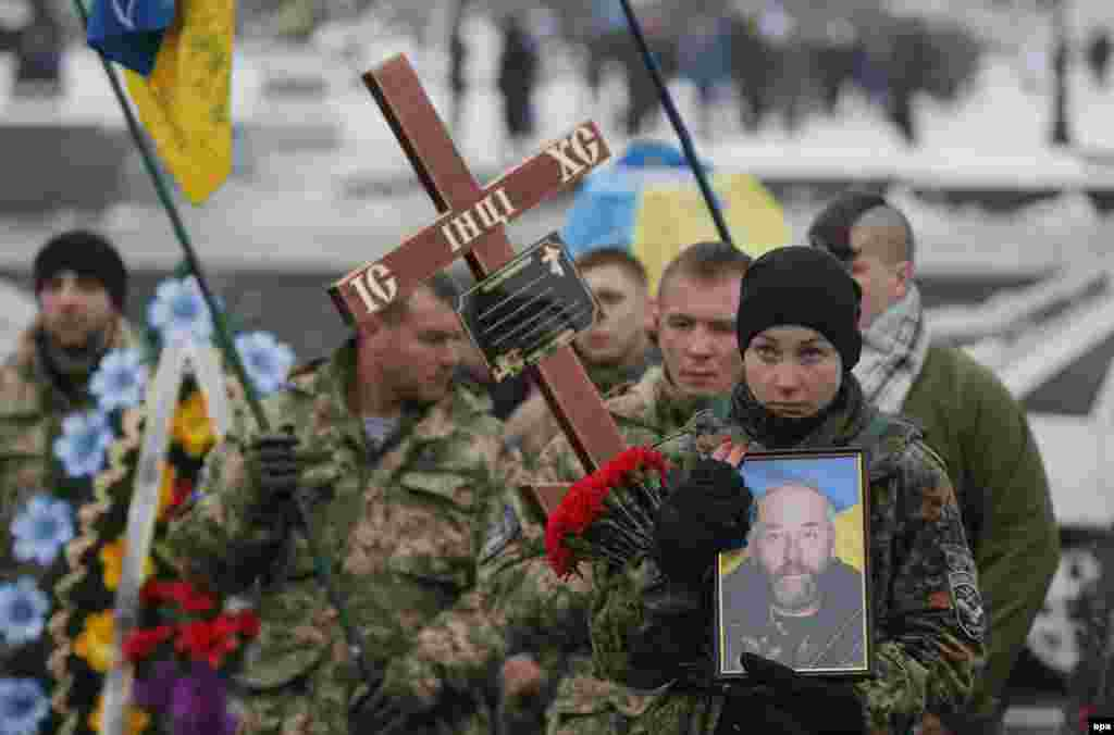 "Bohdanna Nikonenko holds a portrait of her father Serhiy as she takes part in a funeral ceremony for the serviceman from the ""Aydar"" battalion, who was killed in  fighting in eastern Ukraine, on Independence Square in Kyiv on January 20. (epa/Sergey Dolzhenko)"