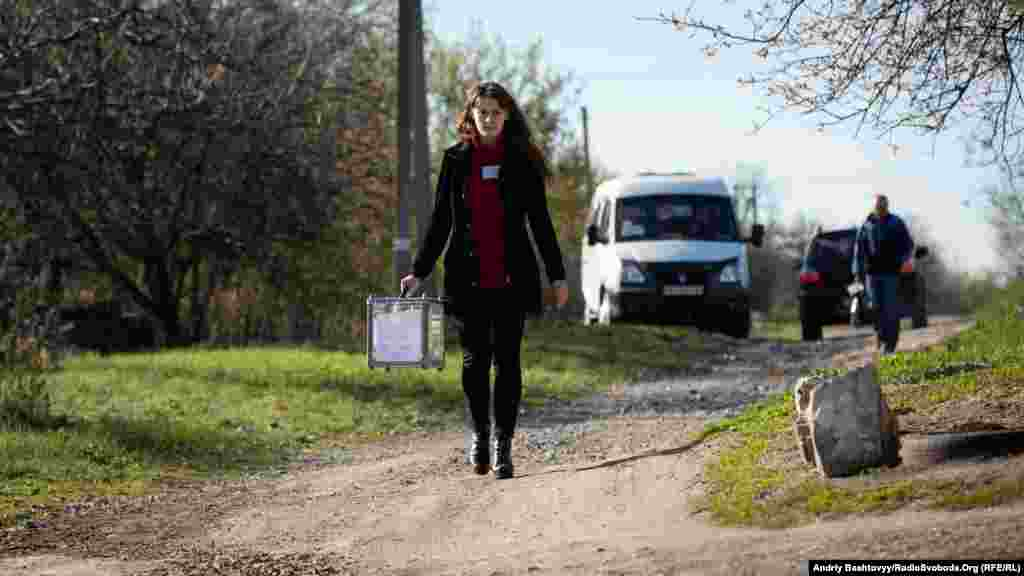 An election official tours the front-line village of Novotroitse in the Donetsk region.