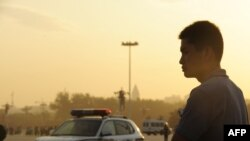 A plainclothes policeman keeps watch on Tiananmen Square at sunrise in Beijing.