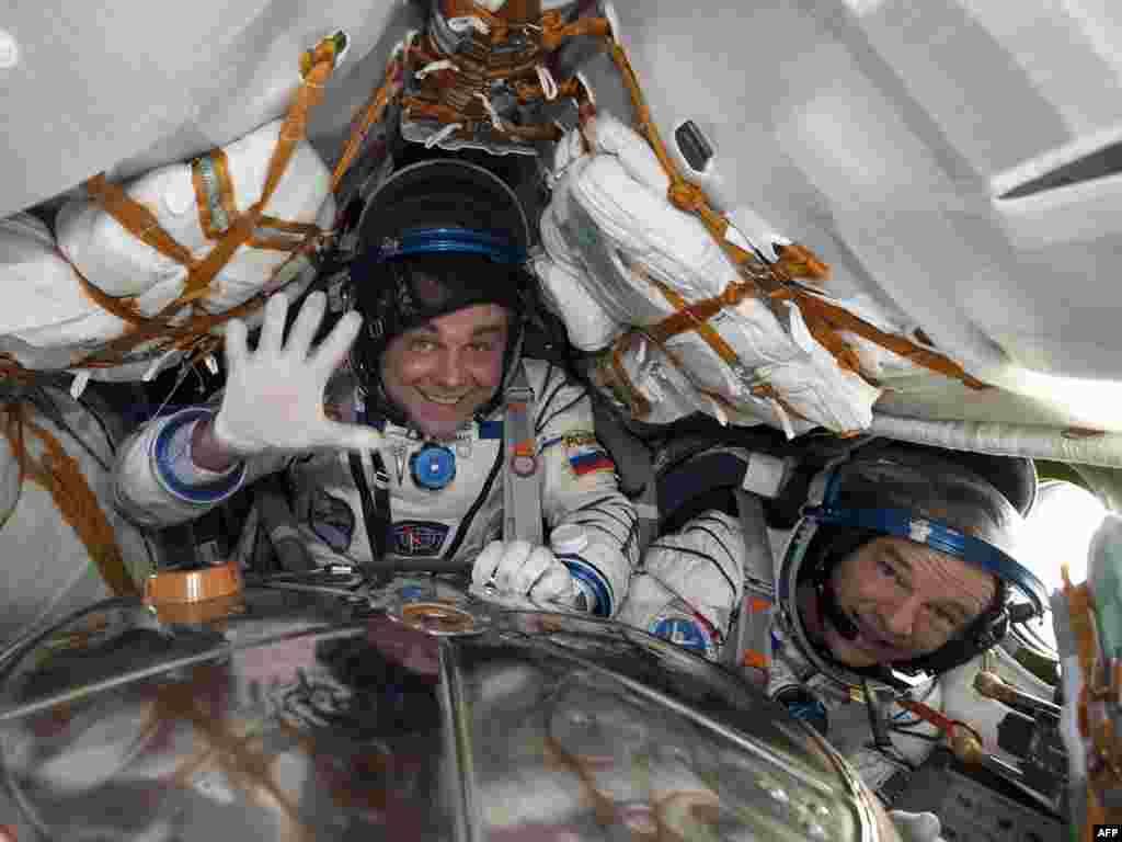 Касманаўты Максім Сураеў (Расея) і Джэфры Ўільямс (ЗША) пасьля прызямленьня ў Казахстане.