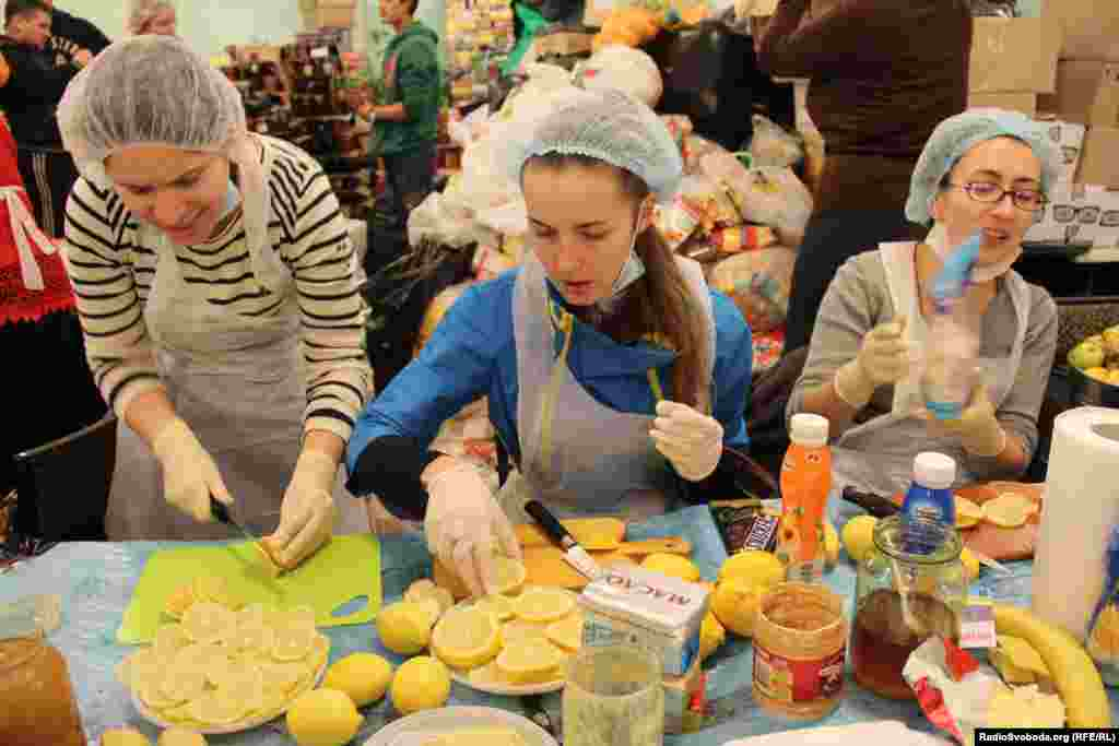 Young women sing Ukrainian folk songs while cutting fruit and preparing sandwiches.