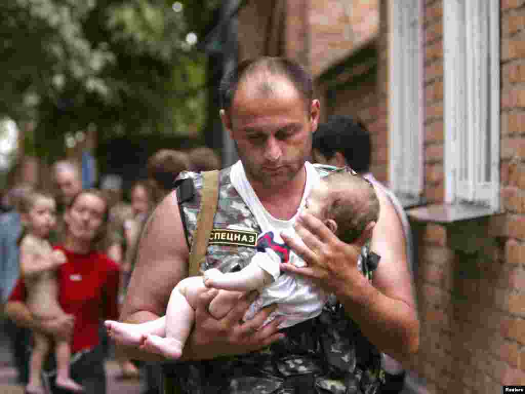 A Russian police officer carries a released baby from the school seized by heavily armed masked men and women in the town of Beslan in the province of North Ossetia near Chechnya, September 2, 2004. REUTERS/Viktor Korotayev
