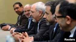 Iranian Foreign Minister Mohammad Javad Zarif (center), flanked by members of his delegation, attends talks over Iran's nuclear program in Geneva on November 22.