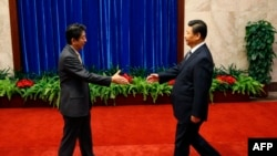 شی جینپینگ، رئیس جمهور چین (راست) و شینزو آبه، نخست وزیر ژاپن در نشست همکاریهای اقتصادی آسیا - پاسفیک
