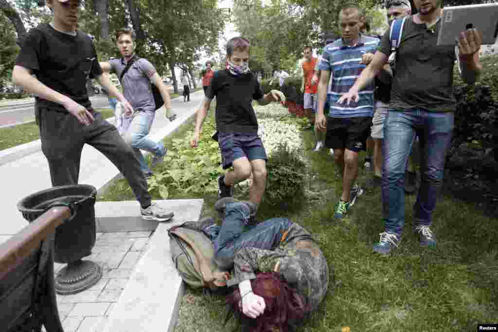 "Youths kick a gay-rights activist during a protest against a bill that would outlaw ""homosexual propaganda"" directed toward minors. Activists say the bill, backed by Russian President Vladimir Putin's allies in parliament, would prohibit all gay-rights rallies and is fueling violence against gays. (Reuters/Maxim Shemetov)"