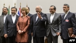 EU foreign policy chief Catherine Ashton (third from left) poses next to Iranian Foreign Minister Mohammad Javad Zarif (third from right) and the Iranian delegation in Geneva after a statement early on November 24 announcing the deal on Iran's nuclear program.