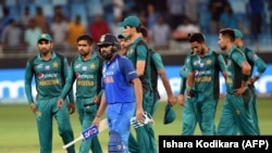 Indian team captain Rohit Sharma (C) and Pakistan team leave the field after India won by 9 wickets during the one day international (ODI) Asia Cup cricket match between Pakistan and India at the Dubai International Cricket Stadium in Dubai on September 23.