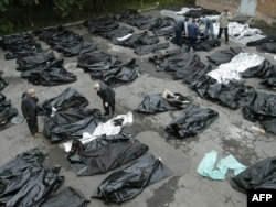 Родственники пытаются опознать тела своих погибших в Беслане близких во дворе морга. Владикавказ, 5 сентября 2004 года.