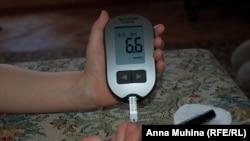 Ребенок, больной сахарным диабетом, измеряет уровень сахара в крови