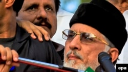 Tahirul Qadri (R), a Pakistani-Canadian cleric, is surrounded by security personnel as he speaks to supporters during protest in Islamabad, Pakistan.