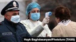 Медична працівниця перевіряє температуру у жінки на в'їзді до міста Вагаршапат, 16 березня 2020 року