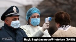 An Armenian medical worker measures the temperature of a woman at an entrance to the city of Vagharshapat as part of the country's measures taken to prevent the spread of the coronavirus