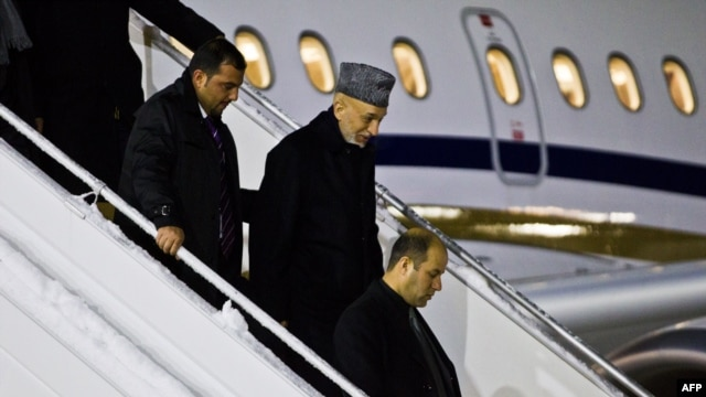 Afghan president Hamid Karzai (second from right) arrives at Gardemoen Airport in Oslo on February 4.