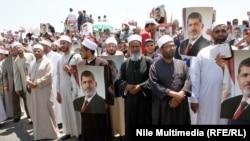 Египеттің бұрынғы президенті Мұхаммед Мурсиді қолдаушылар оның портретін ұстап тұр. Каир, 25 шілде 2013 жыл.