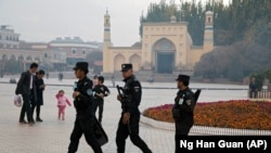 Uyghur security personnel patrol near the Id Kah Mosque in Kashgar in western China's Xinjiang region, in 2017.