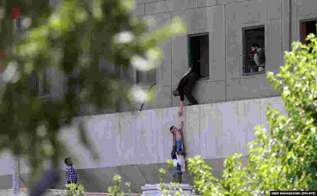 Iranian policemen help civilians flee the parliament building in Teheran. At least 12 people were killed in twin attacks on parliament and the tomb of Iran's former supreme leader Ayatollah Khomeini. June 7, 2017. (EPA-EFE/Omid Wahabzadeh)