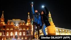 Молодые люди с горящими фонариками смартфонов выражают поддержку оппозиционеру Алексею Навальному на Красной площади. Москва, 14 февраля 2021 года.
