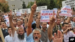 "Muslim protesters hold banners reading "" Dignity, Justice, Identity"" in Pristina"