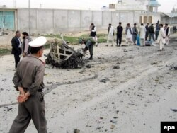 Polițiștii afgani inspectează resturile unei mașini folosite într-un atac sinucigaș cu bombă asupra trupelor canadiene din Kandahar, 30 martie 2006. Bomba a explodat înainte de a ajunge în dreptul convoiului, ucigând sinucigașul și rănind șapte civili.